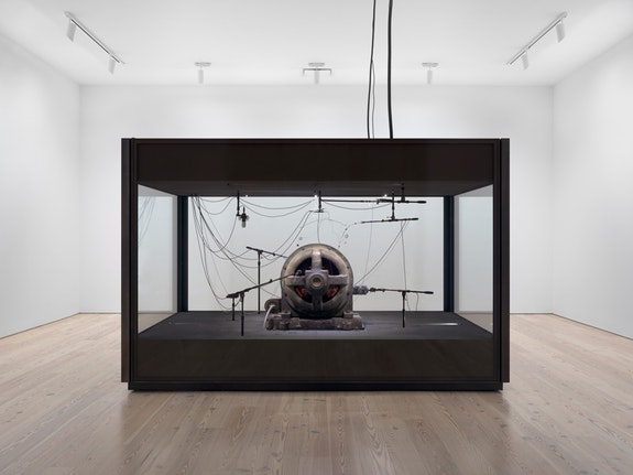 <p>Kevin Beasley, <em>A view of a landscape: A cotton gin motor</em>, 2012-18. Installation view, Whitney Museum of American Art, New York, 2018–2019. GE induction motor, custom soundproof glass chamber, anechoic foam, steel wire, monofilament, cardioid condenser microphones, contact microphones, microphone stands, microphone cables, and AD/DA interface. Courtesy Casey Kaplan, New York. Photo: Ron Amstutz.</p>
