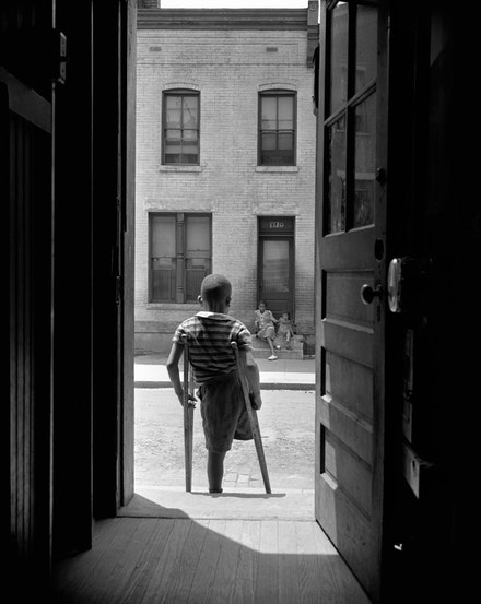 Gordon Parks, <em>Washington, D.C. Young boy standing in the doorway of his home on Seaton Road in the northwest section. His leg was cut off by a streetcar while he was playing in the street, June 1942. </em>Gelatin silver print, printed later. 20 x 16 inches. © and courtesy The Gordon Parks Foundation.