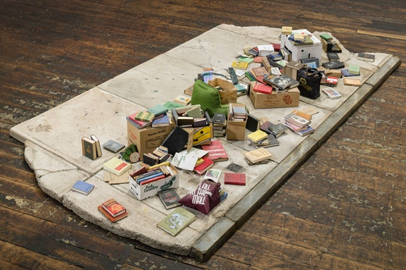 Charles LeDray, <em>Free Public Library</em>, 2015–2019. Paper, cardboard, fabric, thread, acrylic paint, ink, acrylic varnish, acrylic gel medium, brass, patina, bubble gum, glass, metal, wire, wood, cement board, cement, granite, glue, fiberfill, mylar, 10 1/8 x 97 1/8 x 50 1/4 inches. Courtesy the artist and Peter Freeman, Inc. Photo: Nicholas Knight Studio.