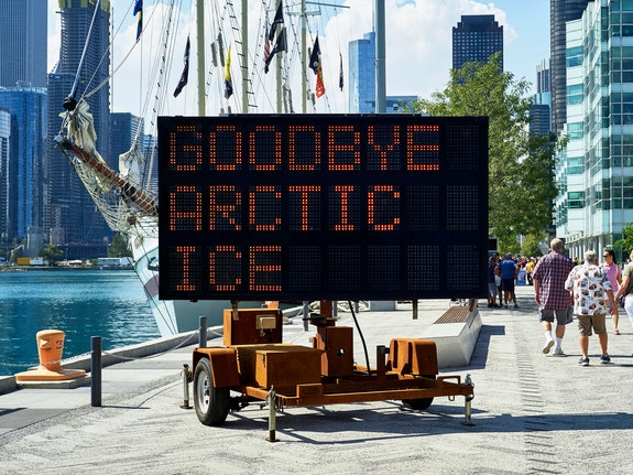 Justin Brice Guariglia, <em>WE ARE THE ASTEROID II</em>, 2018. Solar-powered LED highway message sign, sand-blasted with rusted patina. Text: Timothy Morton 2018. Approx. 15 feet 6 inches x 11 feet 6 inches x 13 feet 3 inches. installation view, Chicago Navy Pier, as part of EXPO Chicago's  IN/SITU OUTDOOR programming. This work was funded with a grant from the Union of Concerned Scientists. The aphorisms that appear on this solar powered LED highway message board were written by eco philosopher and author of