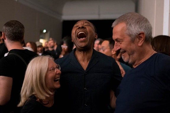 Okwui Enwezor with Ulrich and Marion Wilmes at the concert of Einstürzende Neubauten in Haus der Kunst Munich, June 27, 2015. ©Jörg Koopmann.