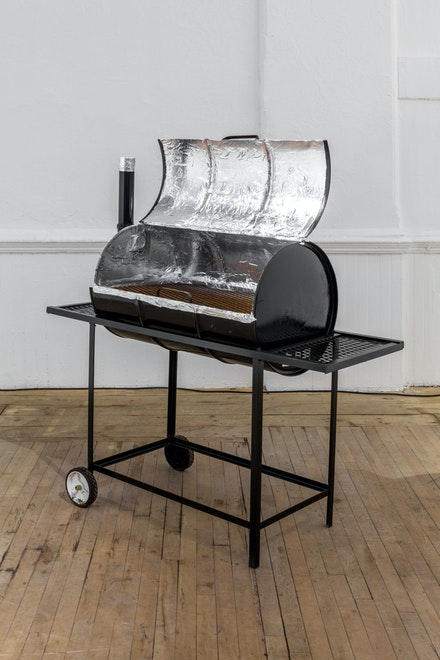 Devin Kenny,<em> Do You Even Talk To Your Neighbors?</em>, 2018. 35-gallon drum grill, photographs, documents, cellular phones, aluminum foil, 56 x 18 1/2 x 52 inches. Courtesy the artist.
