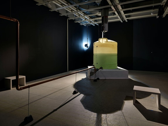 Pope.L, <em>Choir</em>, 2019. Thousand-gallon plastic water-storage tank, water, drinking fountain, copper pipes, solenoid valves, pumps, MIDI controllers, electronic timer module, level-detection probe, flow meters, programmable logic controller, wood, scrim, vinyl letters, microphones, speakers, wires, and sound. Collection of the artist. Courtesy Mitchell-Innes & Nash, New York. Photo: Ron Amstutz. © Pope.L.
