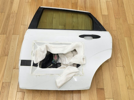 Ann Green Kelly, <em>White Door Little Bag</em>, 2019. Car door, plaster, colored pencil, 10 1/2 × 44 × 37 1/2 inches. Courtesy the artist and Chapter NY, New York. Photo: Dario Lasagni.