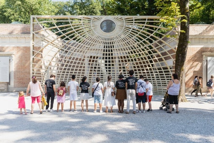 Studio Instute Arts Interns and local families they taught stand in front of Martin Puryear's <em>Swallowed Sun Monstrance</em> and <em>Volute</em>, outside the Venice Biennale's United States pavilion.