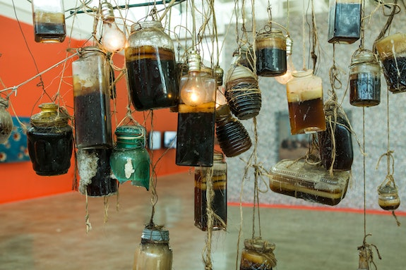 Lauren Bon, <em>Honey Chandeliers</em>, 2007. Honey acquired from war-torn countries around the world, 2001-07. Collected jars, wire, burlap, hessian, light bulbs; dimensions variable. Courtesy the artist and the Metabolic Studio, Los Angeles. Photo by Thom Sanchez.