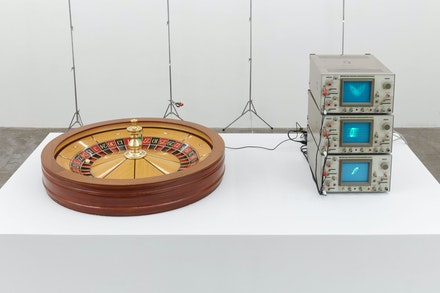 Scott Benzel, <em>Hybrid Monte Carlo</em>, 2020. Regulation roulette wheel, regulation 'pin,' contact mic, motion detector, oscilloscopes, analog electronic circuits based on the equations of Henri Poincaré and Edward Lorenz (top: Lorenz 'Owl Face,' middle: Poincaré diagram, bottom: Poincaré-derived RC 'chaos ladder'), circuits by AST, 73 x 20 x 41 inches. Courtesy Bel Ami, Los Angeles.