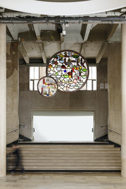 Sara Ouhaddou, <em>Sin ithran, ur mqadan, rousn / Deux astres, au déséquilibre, se brulent</em>, 2020. Circular stained glass, cedar wooden frame, steel strapping, 130 centimeters & 230 centimeters. Exhibition view, <em>Our World is Burning</em>, Palais de Tokyo. Courtesy of the artist. Photo: Aurélien Mole