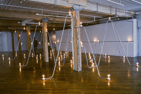 Nancy Holt,<em> Electrical System II: Bellman Circuit</em> (1982). David Bellman Gallery, Toronto, Canada. 3/4 in. steel conduit, lighting and electrical fixtures, light bulbs, electrical wire. Length: 55 ft. (16.7 m); Width: 24 ft. (7.3 m); Height: 9 1/2 ft.(2.9 m) © Holt/Smithson Foundation, Licensed by VAGA at ARS.