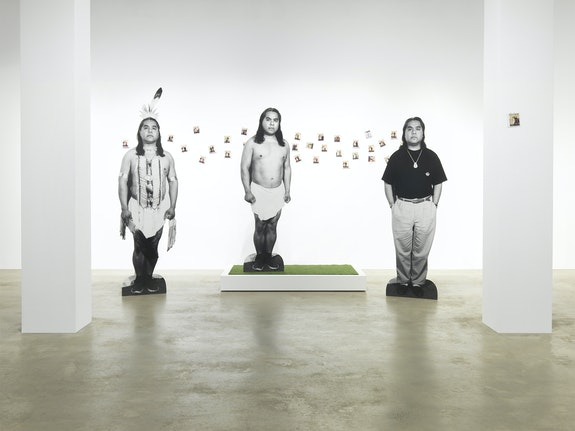 James Luna, <em>Take a Picture with a Real Indian</em>, 1991. Chromogenic silver gelatin, and Polaroid prints, nails, wood, artificial turf, tripod, Polaroid camera, Polaroid film, tape recorder, audio cassette, sound, vinyl text, and chairs, 240 x 76 x 120 inches. Courtesy Garth Greenan Gallery.