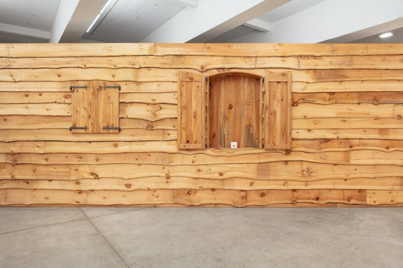 Haim Steinbach, <em>Display #28 - Rustic Wall</em>, 1991. Wood wall; hog pen siding; brass candle snuffer; electronic, plastic tape cassette player, 132 x 690 x 18 inches. Courtesy the artist and Tanya Bonakdar Gallery, New York / Los Angeles. Photo: Pierre Le Hors.