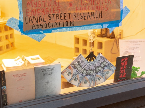 Shanzhai Lyric, <em>Untitled (Window Display)</em>, 2020. Window Cinema poster on repurposed builder's paper, money fan, bootleg books, Canal Street ephemera. Courtesy Canal Street Research Association, New York. Photo: Daniel Terna.