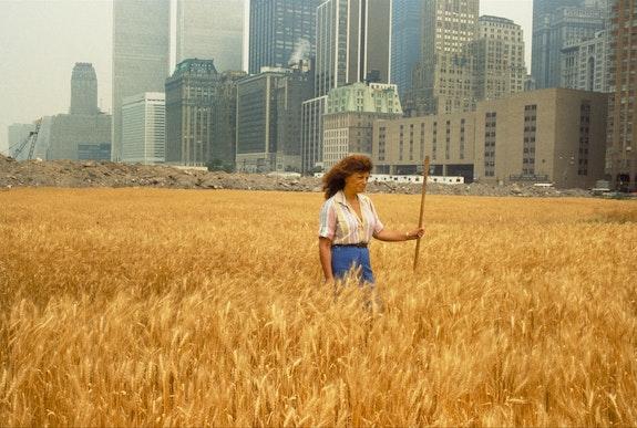 Agnes Denes, <em>Wheatfield - A Confrontation</em>: <em>Battery Park Landfill, Downtown Manhattan</em>, with Agnes Denes Standing in the Field, 1982. © Agnes Denes. Courtesy Leslie Tonkonow Artworks + Projects, New York. Photo: John McGrail.