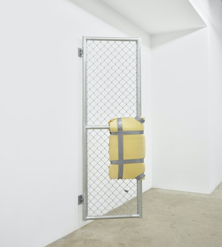 Bat-Ami Rivlin, <em>Untitled (metal gate, yellow foam, duct tape)</em>, 2019. Chain link fencing, metal frame, hinges, polyisocyanurate foam, duct tape, hardware, 84 1/2 x 5 x 24 inches. Courtesy M 2 3, New York.