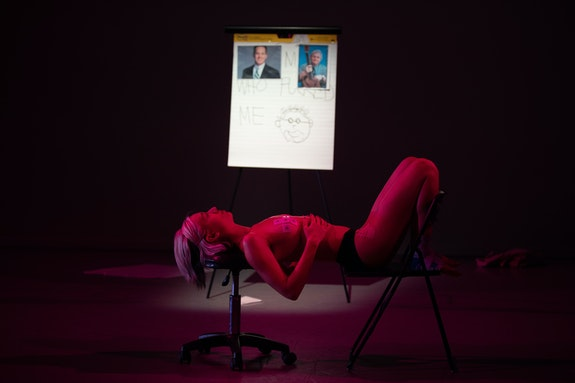 Audre Wirtanen performing <em>DX ME FIX ME</em>, Gibney Dance, 2020. Photo: Scott Shaw.<br><em>Audre, a thin white hypermobile femme, lies on her back, balancing on a medical office stool and folding chair. Her shins press against the back of the chair while her hands rest on her ribcage. Pink light bathes her entire body while a blurry easel collaged with pictures of doctors, a drawing, and text is lit bright white in the background. The easel says THE MEN WHO FUCKED ME. Audre is in her underwear with ECG electrodes stuck to her breasts like medical pasties. Her expression is heavy and silent.</em>