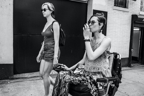 Audre Wirtanen and Laura Tuthall, 2019. Photo: Bryan Bisordi.<br><em>A black and white photo taken on a hot NYC summer day. Audre and Laura are in profile on a mission down the sidewalk. Audre, in the background, walks beside Laura rolling in their wheelchair. They both wear sunglasses, summer clothes, and short hair. They are both Hypermobile, white, and femme. Laura inhales from a medical marijuana vaporizer as they traverse together, pensive, serious, and sweaty.</em>