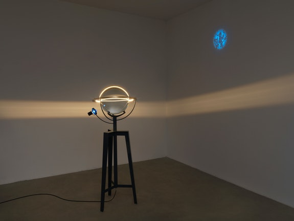 Olafur Eliasson, <em>Model for decelerated light</em>, 2021. Steel tripod, glass sphere, coloured glass sphere (blue), brass ring, aluminium, paint (black), LED light, ballast, 65 3/4 x 29 1/2 x 23 5/8 inches. Courtesy the artist and Tanya Bonakdar Gallery, New York / Los Angeles.