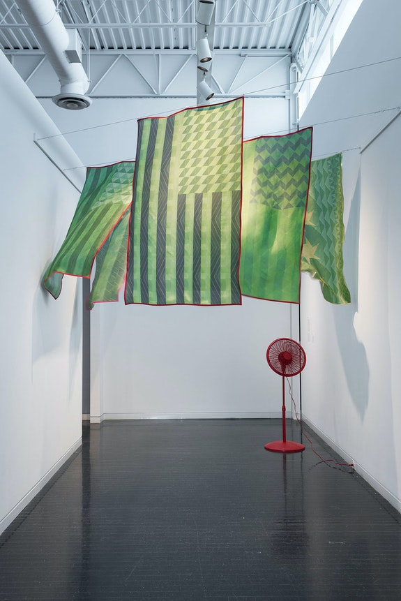 Edra Soto, <em>Tropicalamerican (US I, II, III, PR, CH)</em>, 2014. Inkjet prints on silk, plastic fan, spray paint. 67 x 43 inches. Installation in the Elmhurst Museum. Photo: James Prinz. Courtesy the artist.