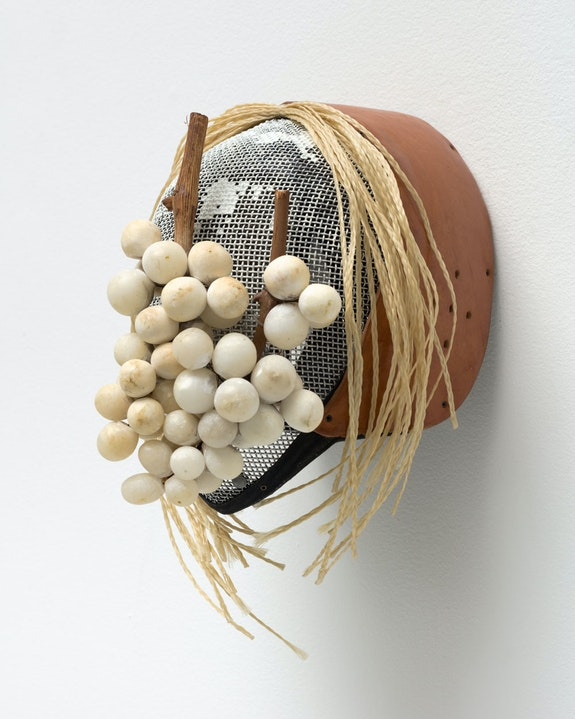 Allison Janae Hamilton, <em>Mask with Braids and Table Grapes</em>, 2021. Vintage metal and leather fencing mask, marble, horse hair, 15 × 12 × 11 inches. Courtesy the artist and Marianne Boesky Gallery, NY and Aspen. © Allison Janae Hamilton. Photo credit: Lance Brewer.