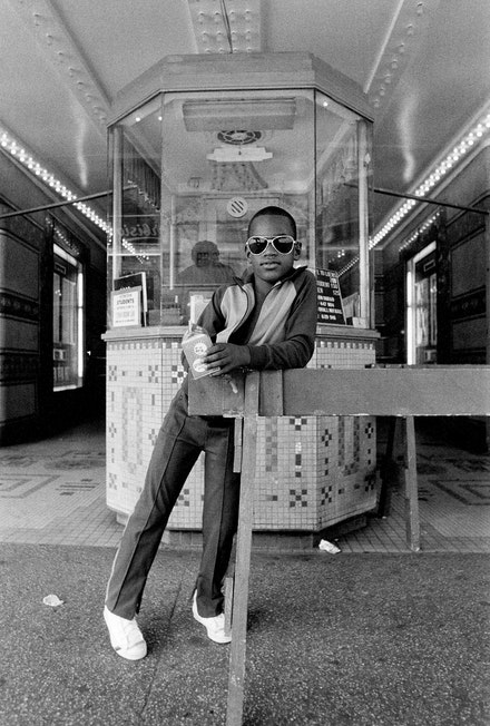 Dawoud Bey, <em>A Boy in Front of the Loew's 125th Street Movie Theater, Harlem, NY from Harlem, U.S.A.</em>, 1976. Gelatin silver print (printed 2019), 14 x 11 inches. Collection of the artist; courtesy Sean Kelly Gallery, New York; Stephen Daiter Gallery, Chicago; and Rena Bransten Gallery, San Francisco. © Dawoud Bey.