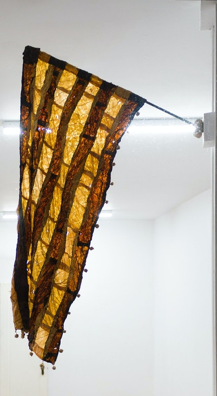 Gabrielle L'Hirondelle Hill, <em>Dispersal</em>, 2019. Virginia tobacco, Perique tobacco, thread, seed pods, support stocking, and found pole, 43 x 14 5/16 inches. Courtesy the artist and Unit 17, Vancouver, and Cooper Cole, Toronto © Gabrielle L'Hirondelle Hill.