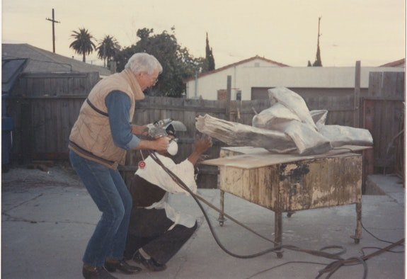 Jack Brogan spraying heated metallic mist at a Lynda Benglis knotted cloth piece