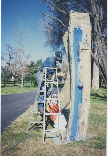 Jack Brogan (typically hidden) putting finishing touches on a Roy Lichtenstein install at the Ray Stark ranch, 1994.