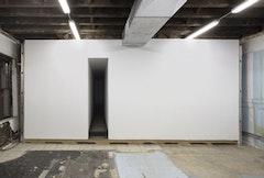 Klara Liden, Elda för kråkorna, (2008). Installation view: sheetrock, aluminum, studs, cardboard, tarpaper, mesh, couch, night light, seeds, lettuce, pigeons.