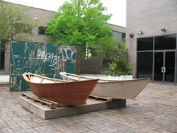 Twi Liberum Dories and four sheets of repurposed and stenciled plywood on display in the courtyard of the Neuberger Museum in Purchase, New York.  Photo by James Trimarco.