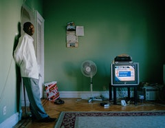 Alam Adam stands in the living room of his Brooklyn home, as poll results from the 2008 election appear on television. Photo by Kelly Kollar.