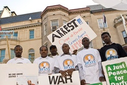 Members of the Darfur People's Association of New York hold signs encouraging the arrest of Sudanese president Omar al-Bashir at a rally in D.C.