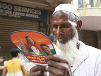 An Indian voter reads a political pamphlet distributed during a rally of the Indian National Congress in the western Indian city of Mumbai. Photo by Al Jazeera English.