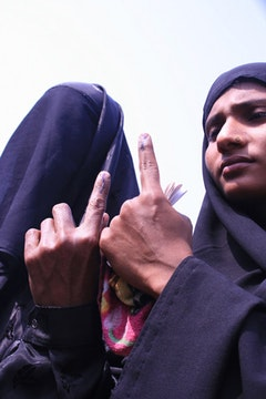 Two Muslim women voters showing their marks on finger after voting at Samaguri in Nagaon district of Assam. Photo by Diganta Talukdar.