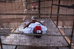 Man sleeping on cart near Greyhound station, Philadelphia. Credit <a href=