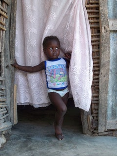 A Haitian boy stands in a hut with new concrete flooring, laid by missionary workers. Photo by Kaitlin Failing.
