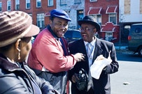 Reverend Robert Jackson, left, jokes with a waiting senior and a Brooklyn College student in front of their building during the Senior Pantry.  Photos by Natalie Keyssar.