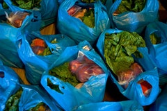 Blue plastic bags full of vegetables, fruits and chicken line the floor if the Brooklyn Rescue Mission.