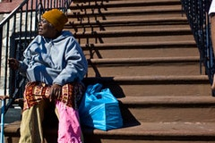 A woman rests on a stoop with her bag of food from the Rescue Mission.