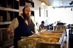 Excecutive director Alexander Rapaport stands behind a table full of steaming food before opening on a Wednesday night in April.  Photos by Natalie Keyssar.