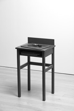 "Vija Celmins, ""Table with Gun"" (2009-10). Table: wood and acrylic, 3 found tablets, 1 made tablet: bronze, acrylic, alkyd oil, and pastel, 1 made gun: bronze, alkyd oil. 33 × 181/4 × 143/4 inches. Courtesy of the artist and David McKee Gallery."