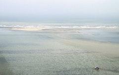 A shrimper heads towards a slick of oil off the coast of Venice, Louisiana. Photo by P.J. Hahno.