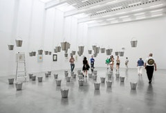 "Rivane Neuenschwander, ""Chove Chuva/Rain Rains"" (2002). Aluminum buckets, water, steel cable, ladder, dimensions variable. Installation View, The New Museum. Photos by Benoit Pailley."
