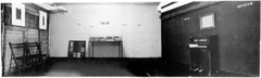 "MARCEL BROODTHAERS, The Inner Room of Section Cinéma, 1972, Burgplatz, Düsseldorf. Montage comprises of two photographs of the two adjacent walls and a photograph of the white brick wall with the sealed vitrine containing the ""catalogue raisonné"" and the stenciled ""figures"". On the floor in front of the piano is the stenciled ""fig.12"". Courtesy of the Estate of Marcel Broodthaers and Marian Goodman Gallery, New York"
