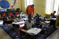 A teacher helps students with classwork at Bed-Stuy's Children of Promise. Photos by Nick Childers.