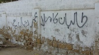 "In Urdu, the wall says ""Mulla Omar of the Taliban is the devil incarnate."" Photos by Rehan Ansari."