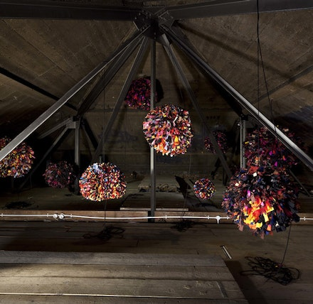 "Phyllida Barlow, ""RIG: untitled; pompoms,"" 2011. Fabric, paper. 15 large fabric balls. Overall installed dimensions: 109 x 341 x 316 7/8"". Work in situ. Dimensions variable. Installation view. Hauser & Wirth. London, Piccadilly, 2011. © Phyllida Barlow. Courtesy the artist and Hauser & Wirth. Photo: Peter Mallet."