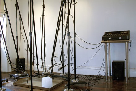 "Paul Kos, ""The Sound of Ice Melting,"" 1970. Two 25 lb. blocks of ice, 8 boom microphone stands, 8 microphones, mixer, amplifier, 2 large speakers, and cables. Dimensions variable. Courtesy Nyehaus."