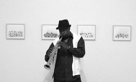 "Joe McPhee in front of ""Commandment"" drawing series by Alain Kirili at Akira Ikeda Gallery/NY 2012. Photo: Takuma Kanaiwa."