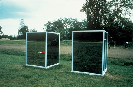 "Dan Graham, ""Two Adjacent Pavilions,"" 1982. Two structures: two-way mirror, glass, steel. 98 3/4 x 73 1/5 x 73 1/5"". Courtesy Marian Goodman Gallery."